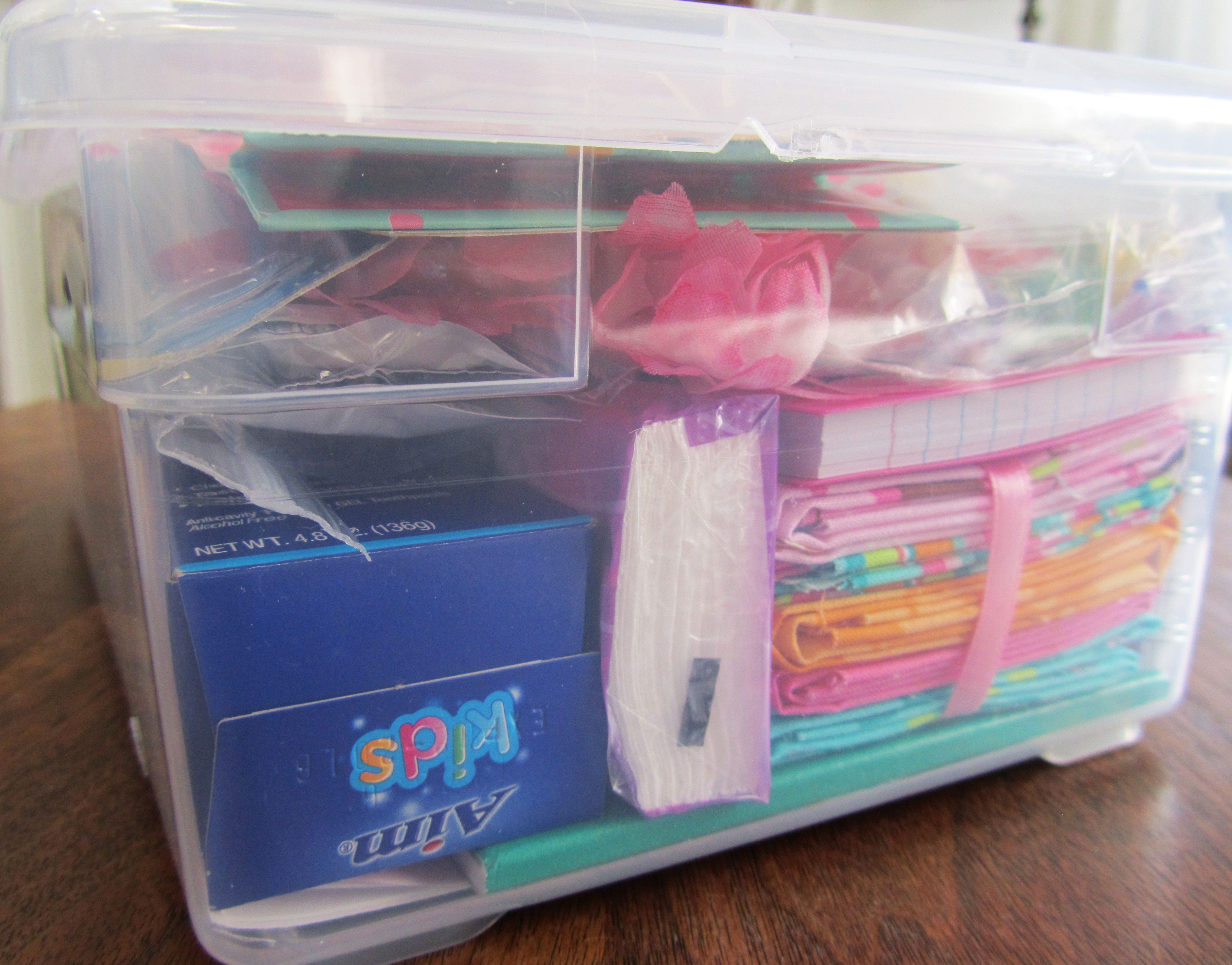 Side view of same box for girl age 10-14 showing material for sewing, school supplies, and other items. Check with OCC about including toothpaste because it's not allowed in some countries.