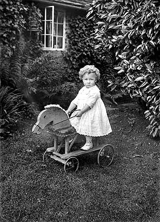 Small child riding toy horse on wheels in the garden, Warwickshire. (English Heritage Viewfinder.)