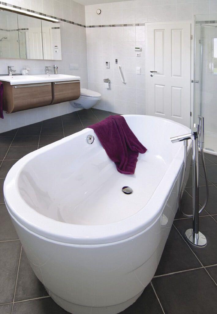 Modernes Badezimmer Mit Badewanne Freistehend Fliesen Boden Grau   Ideen  Einrichtung Winkelbungalow WeberHaus Fertighaus   HausbauDu2026