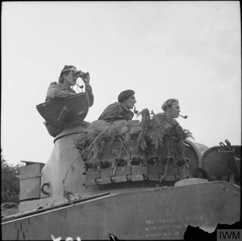 A Sherman tank crew, smoking a variety of pipes, awaits the order to advance near Argentan, 21 August 1944.