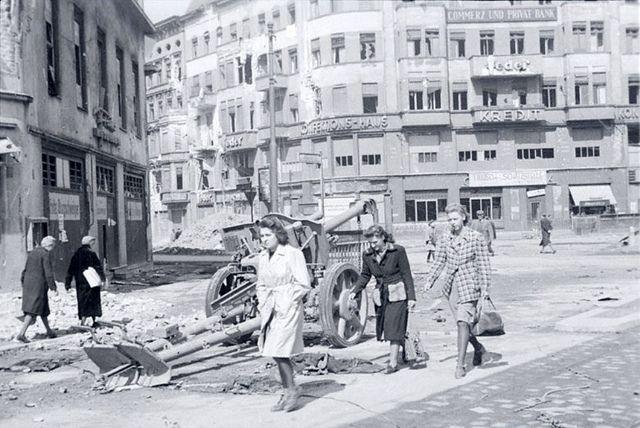 1945, Allemagne, Berlin, des femmes passent à côté d'un PaK abandonné en pleine rue