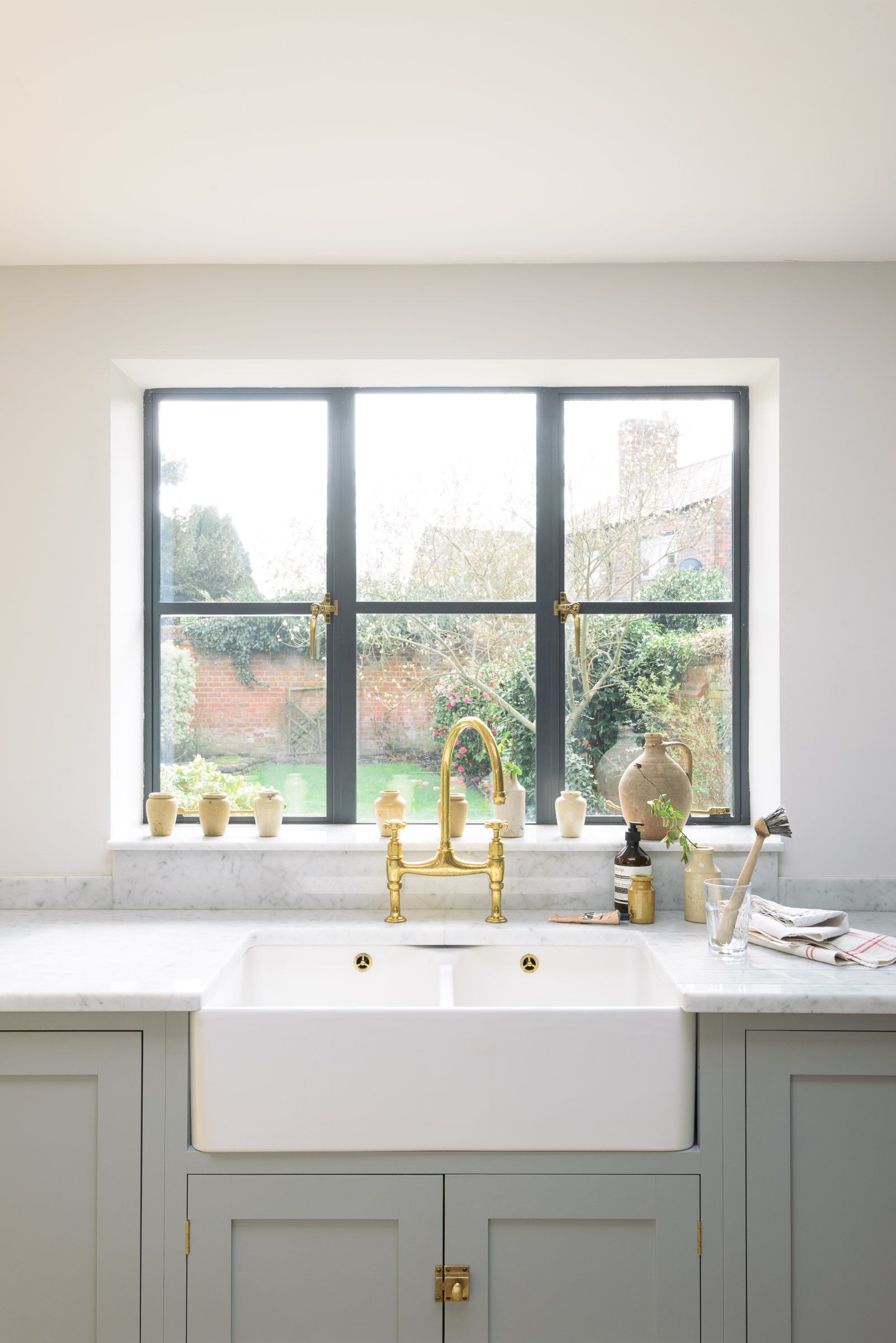 Window for kitchen  a double belfast sink and devol aged brass taps are the perfect
