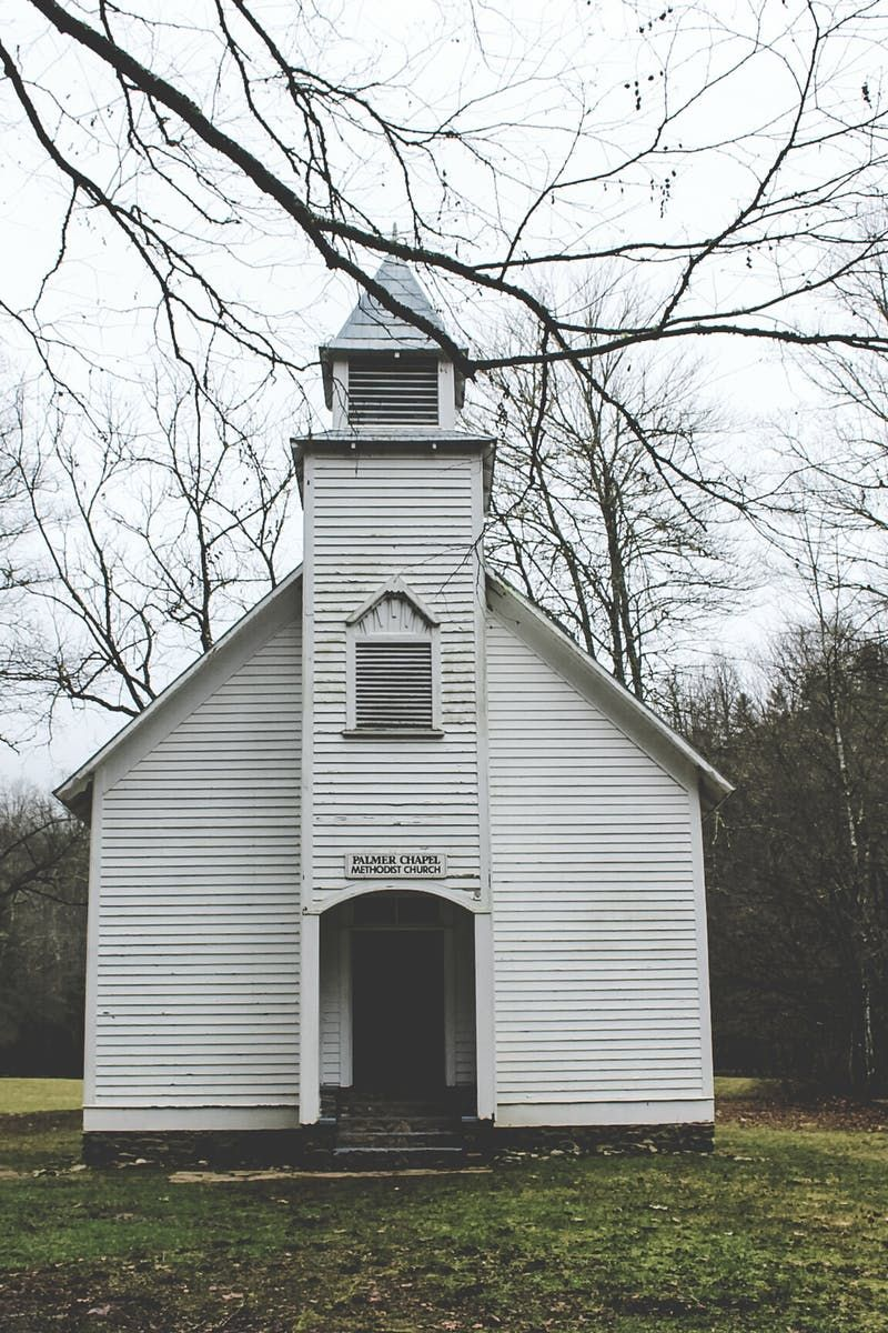 Download this free photo from Pexels at https://www.pexels.com/photo/white-and-black-wooden-chapel-surrounded-by-green-grass-116225/ #landscape #sky #trees