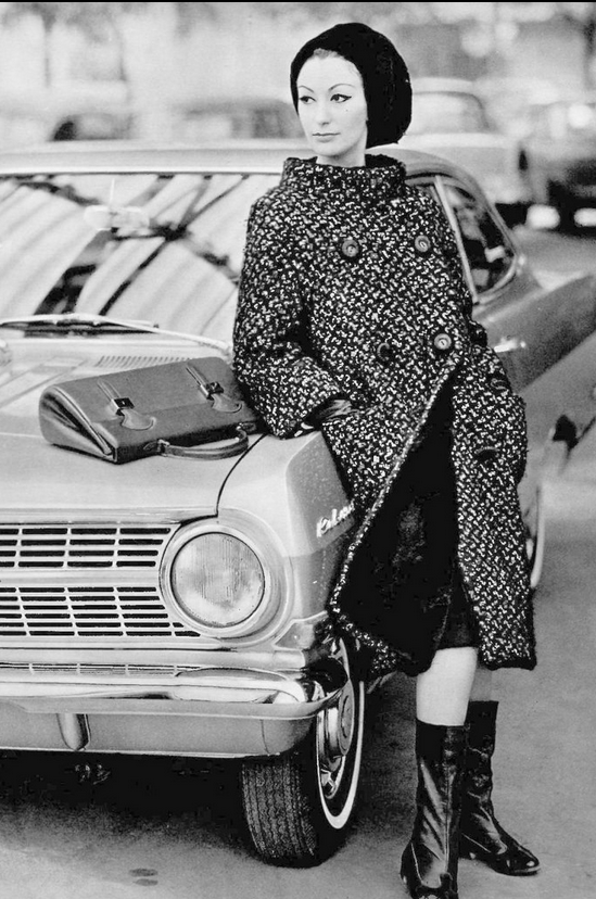 1963 Model in black and white tweed coat, stand-up collar, double buttons, lined in otter fur, worn with otter fur beret, by Pierre Balmain, purse and boots by Durer,