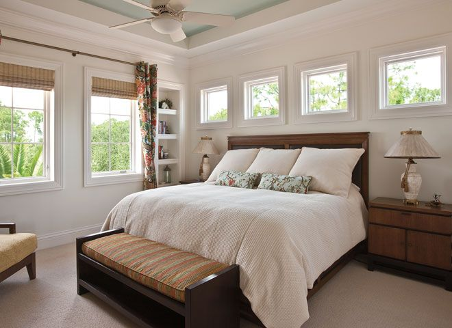 Lots of windows welcome in natural light in a relaxing master suite featured pella architect Master bedroom window size