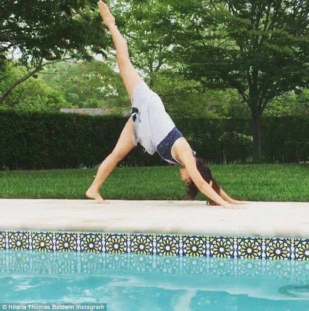 Hilaria Baldwin demonstrates yoga moves by swimming pool ...