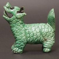 A Kangxi or Yongzheng Porcelain Model of a Mythical Beast c.1700-1735. The Form Constructed of Several Different Moulded Sections and Simply put Together. It has a Thin Pale Green Glazed Body and Head with the Eyes and Horns Picked out in Iron-Black.