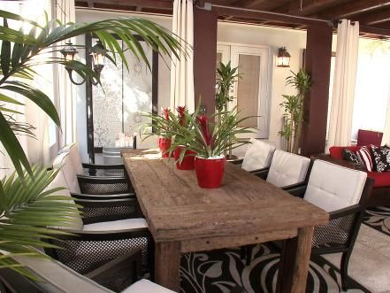 Reclaimed+lumber+creates+a+one-of-a-kind+table+that+will+accommodate+up+to+eight+guests.+Weather-resistant,+floor-to-ceiling+draperies+and+beautifully+patterned+rugs+make+this+outdoor+space+feel+like+an+extension+of+the+indoors.++