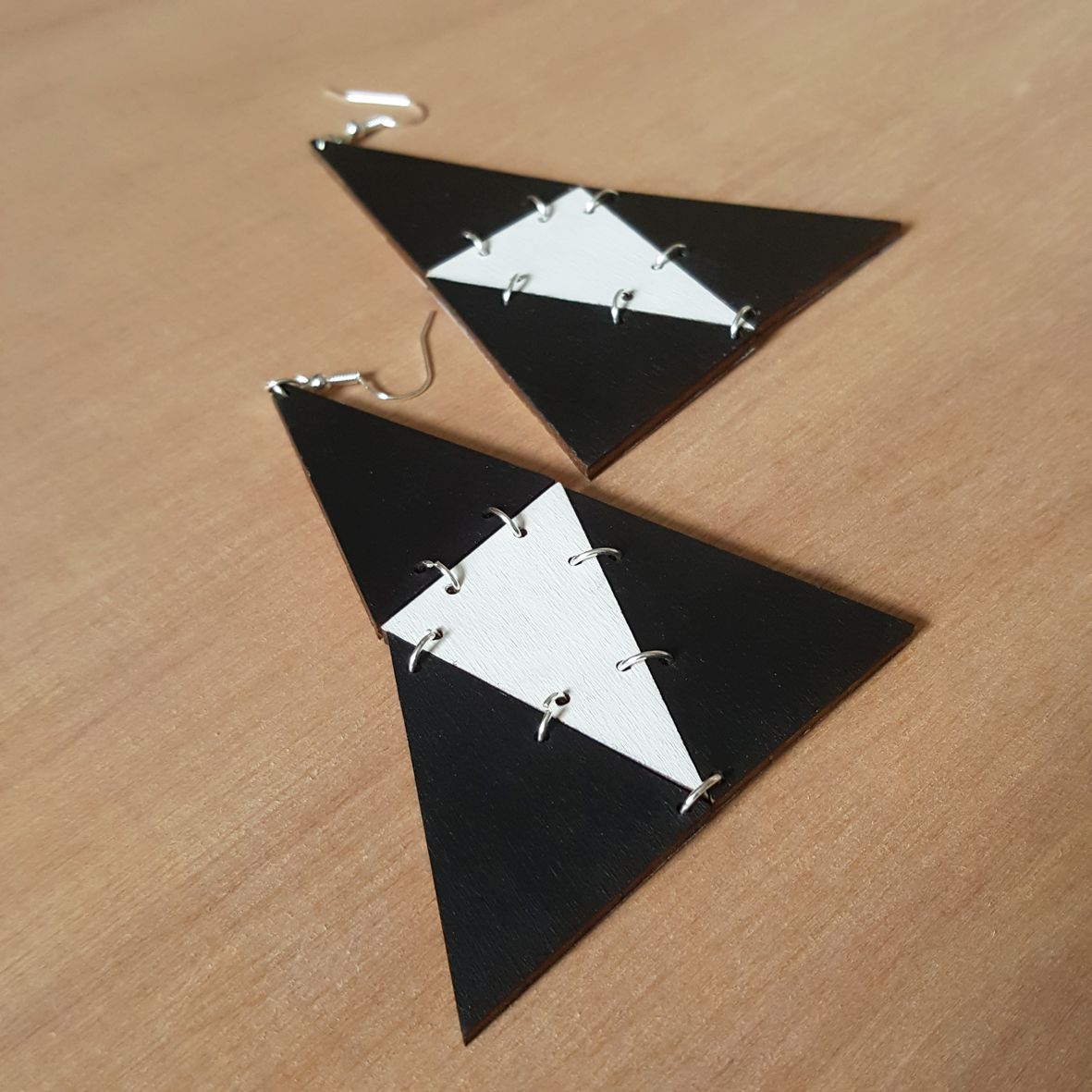 Unique earrings made of little triangles to become an elegant addition to any outfit. Make a perfect gift for various occasions (or with no occasion at all). Made of wood and painted in white and black. Finished with silver-plated elements. Approximate size - 6.5 x 8.5 cm. Laser cut product. Made in Britain.