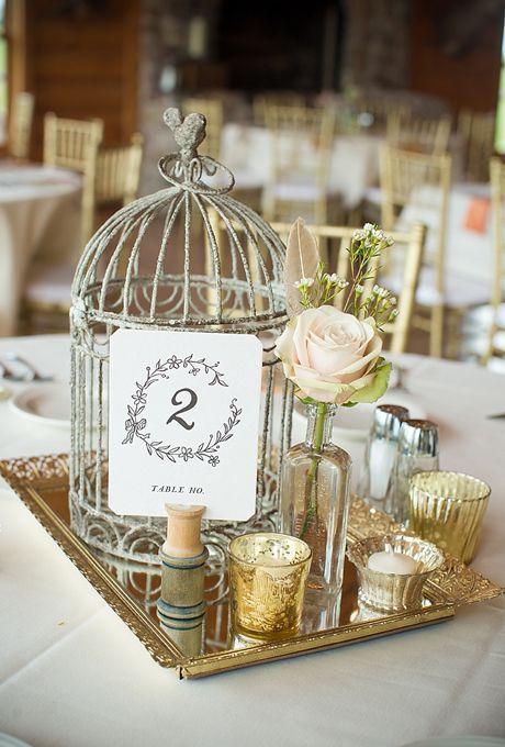 Simples centros de mesa florales. Una jaula para bodas en una bandeja de oro. Una rosa y algunos objetos vintage, como una jaula de hierro y velas de té en contenedores de vidrio de mercurio, se unen para crear un centro de mesa vintage.
