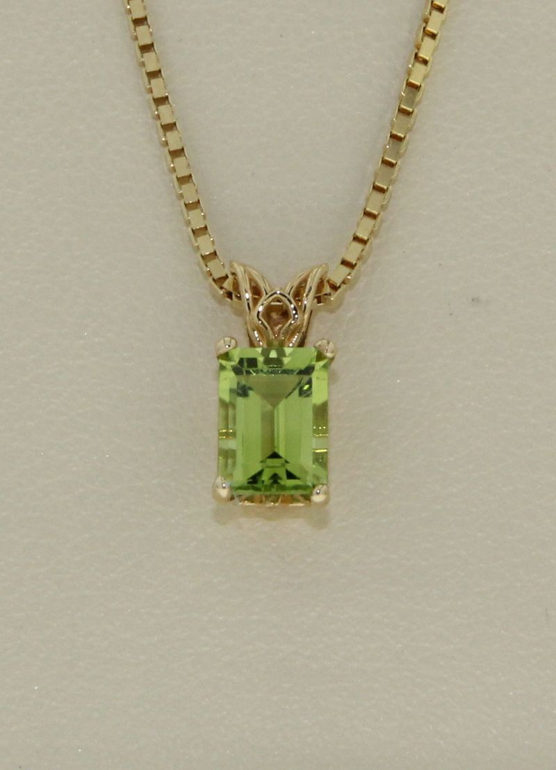 Peridot xmm solitaire pendant set with one emerald cut shaped