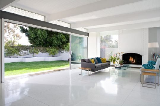 Living Room With A Large Glass Sliding Door, White Tile Floor, Fireplace,  And