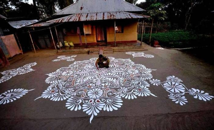 Village woman in Bengal decorating her simple courtyard with Alpana.