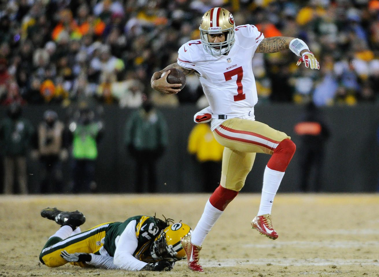 NFC Wildcard Playoff-San Francisco 49ers at Green Bay Packers -- Jan 5, 2014; Green Bay, WI, USA; San Francisco 49ers quarterback Colin Kaepernick (7) runs with the ball past Green Bay Packers cornerback Davon House (31) in the second quarter during the 2013 NFC wild card playoff football game at Lambeau Field. (Benny Sieu-USA TODAY Sports)