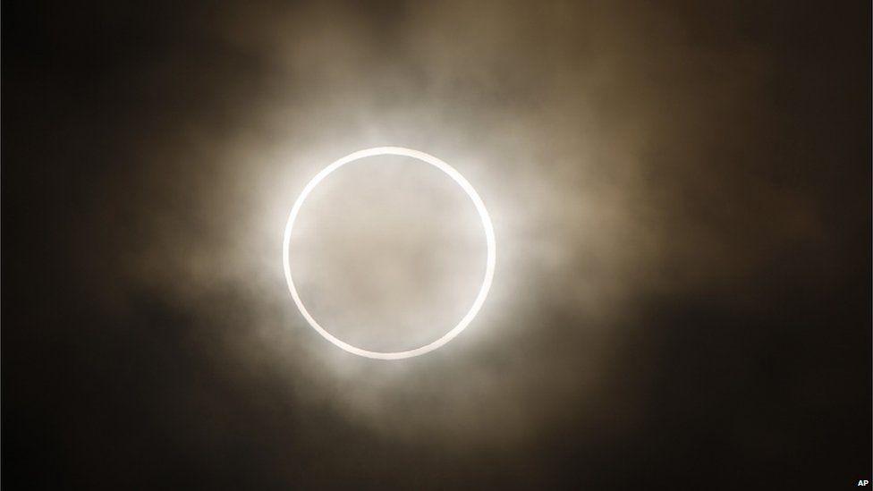 The annular eclipse over Yokohama, near Tokyo in Japan, a dazzling light illuminating an otherwise pitch dark sky.