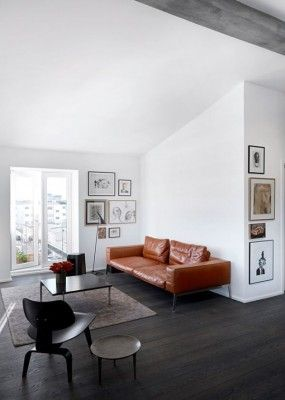 Minimalist Living Room With Leather Sofa Dark Floors Vaulted Ceiling And Exposed Neutral Gallery Wall