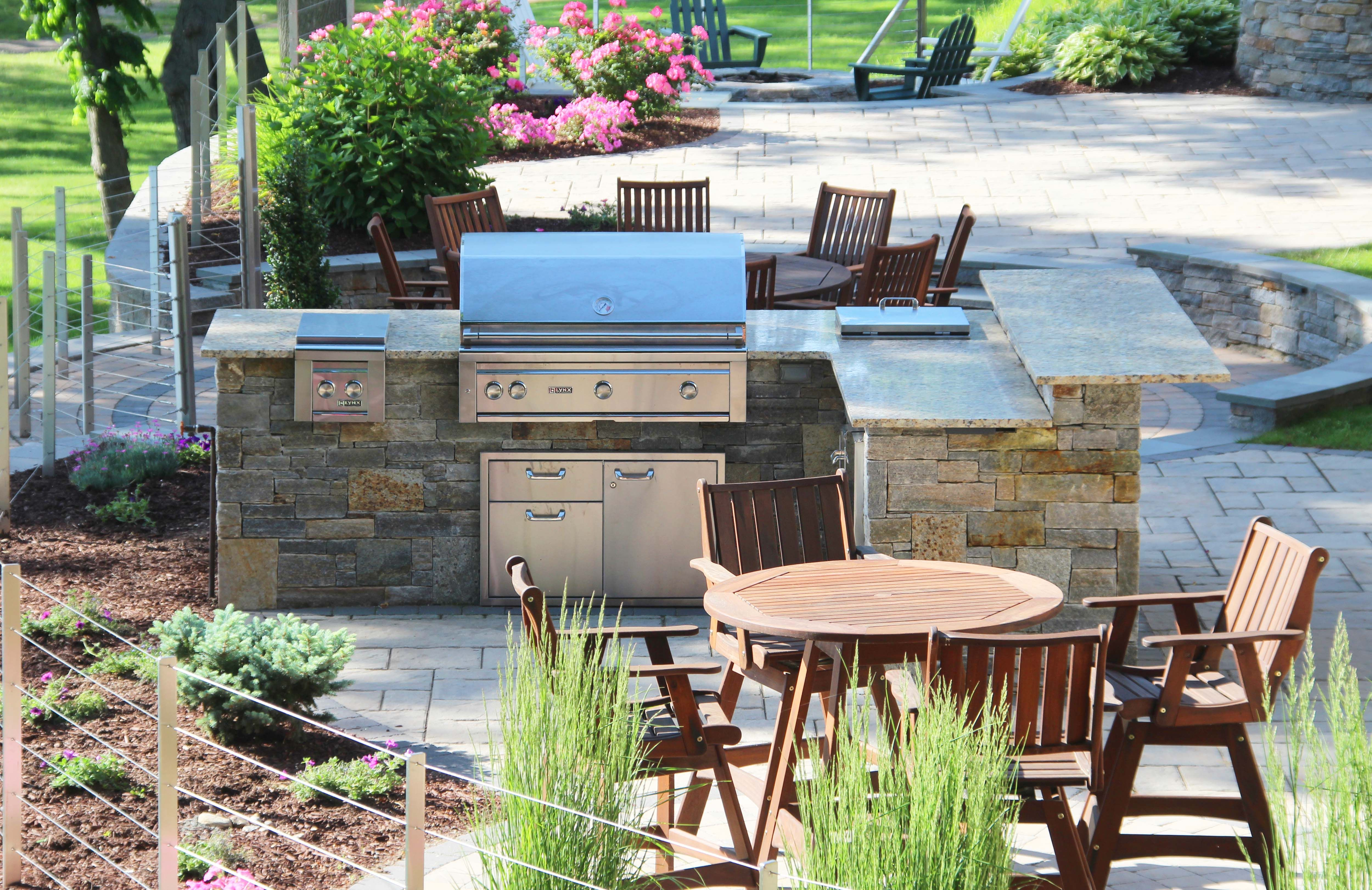 a natural stone outdoor kitchen with a grill fridge side burner and storage with a granite on outdoor kitchen natural id=52141