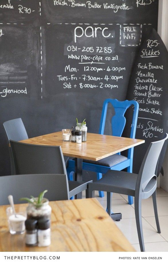 parc cafe interior black painted wall with chalk writings blue chairs wood tables - Painted Wood Cafe Decoration