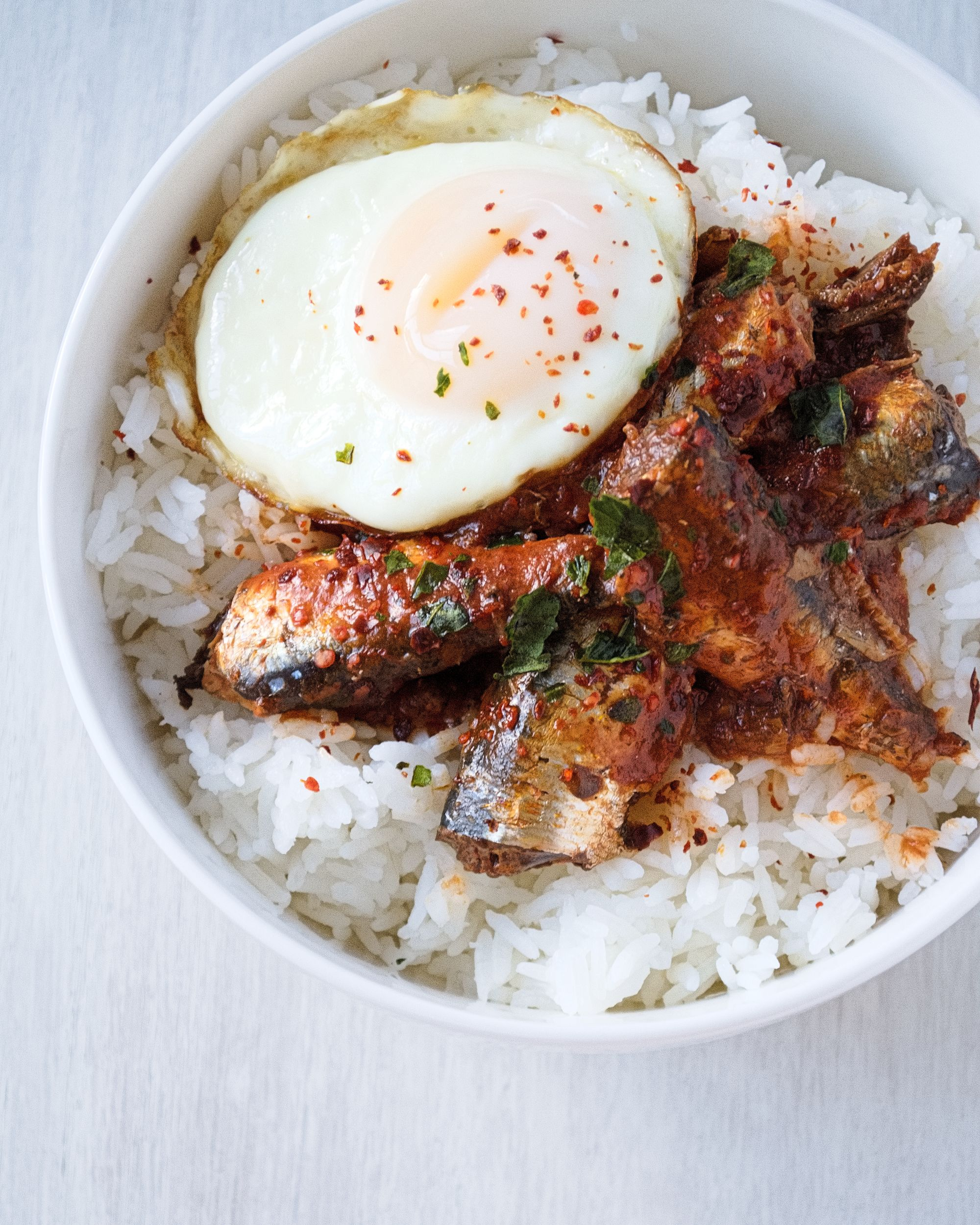 This sardine rice bowl with an egg on top features canned sardines ...