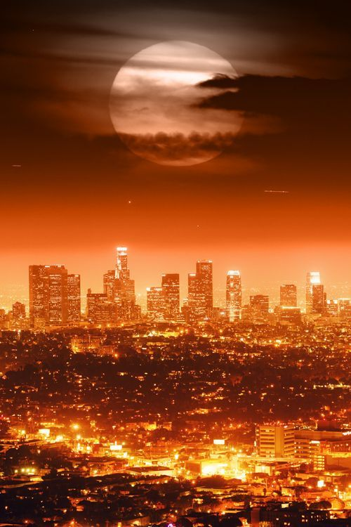 Dramatic full moon over Los Angeles skyline at night