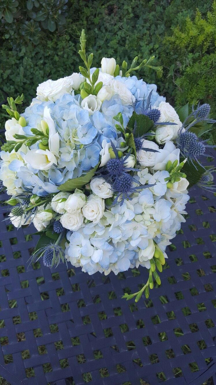 Light blue hydrangea, blue thistle and white spray rose bridal bouquet. #whitebridalbouquets