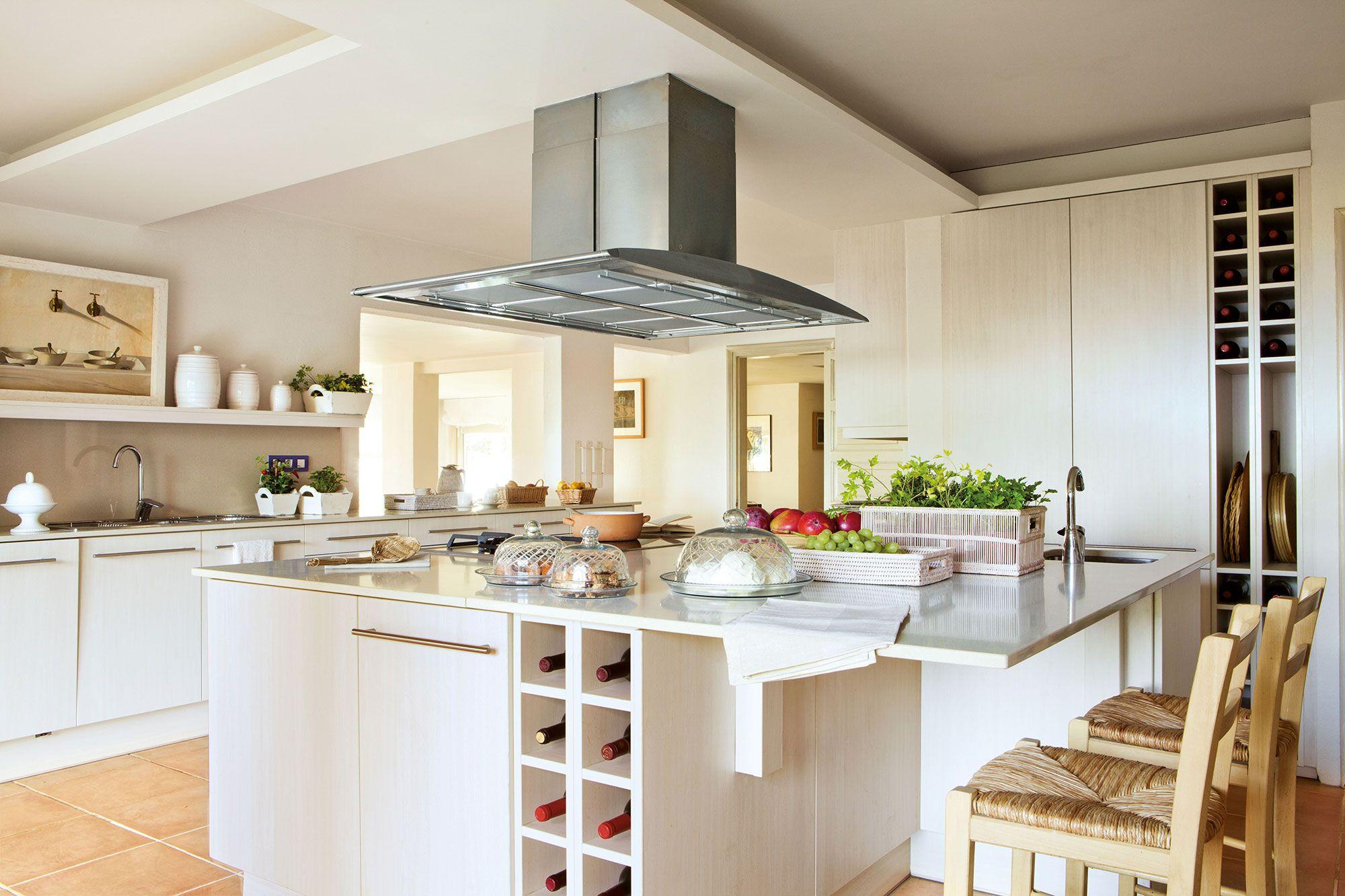 Cocina amplia y luminosa con mobiliario blanco y encimera de acero ...