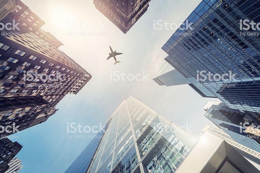 """Skyscraper with a airplane silhouette in the sun, New"