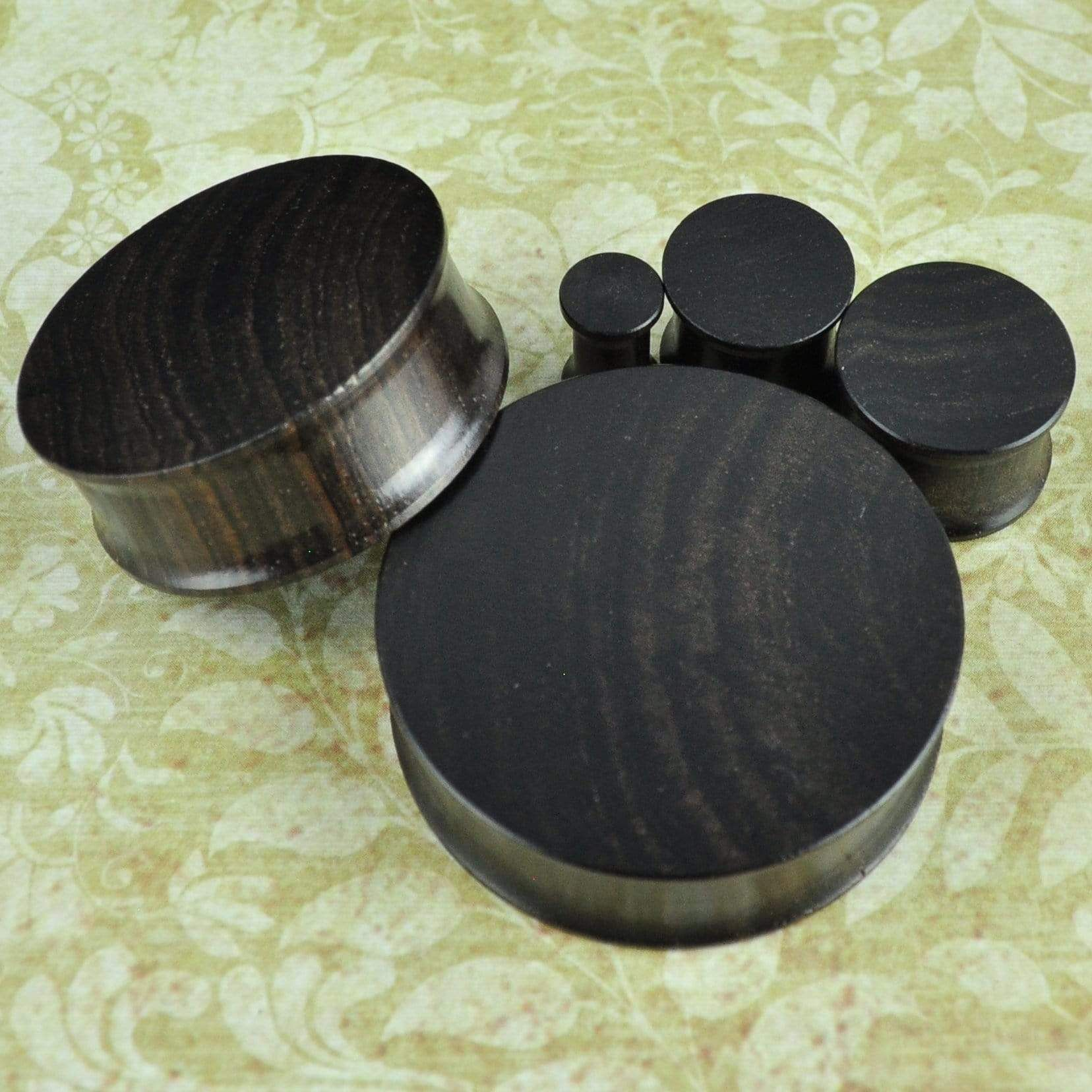 Quantity: Sold as 1 pair (2 pieces) Style: Round cut plug, flat sides Material: Ebony wood Flare: Double flare Size Options: 6-38mm (upon availability) Size: Size ordered is wearable area +/- 1mm Wearable Width: 7mm Natural Material: SIZES ARE NOT EXACT; CAN BE +/- 1MM Natural Material: COLORS AND PATTERNS MAY VARY Lightweight rich dark ebony wood double flare plugs Made of rich-colored dark ebony wood, these double flare plugs give off an earthy vibe. The innate imperfections of the wood make e
