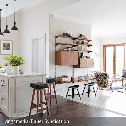 Eine Gemütliche Landhausatmosphäre Wird Durch Die Weiße Kücheninsel Und Den Dunklen  Holzboden Geschaffen. Der Boden
