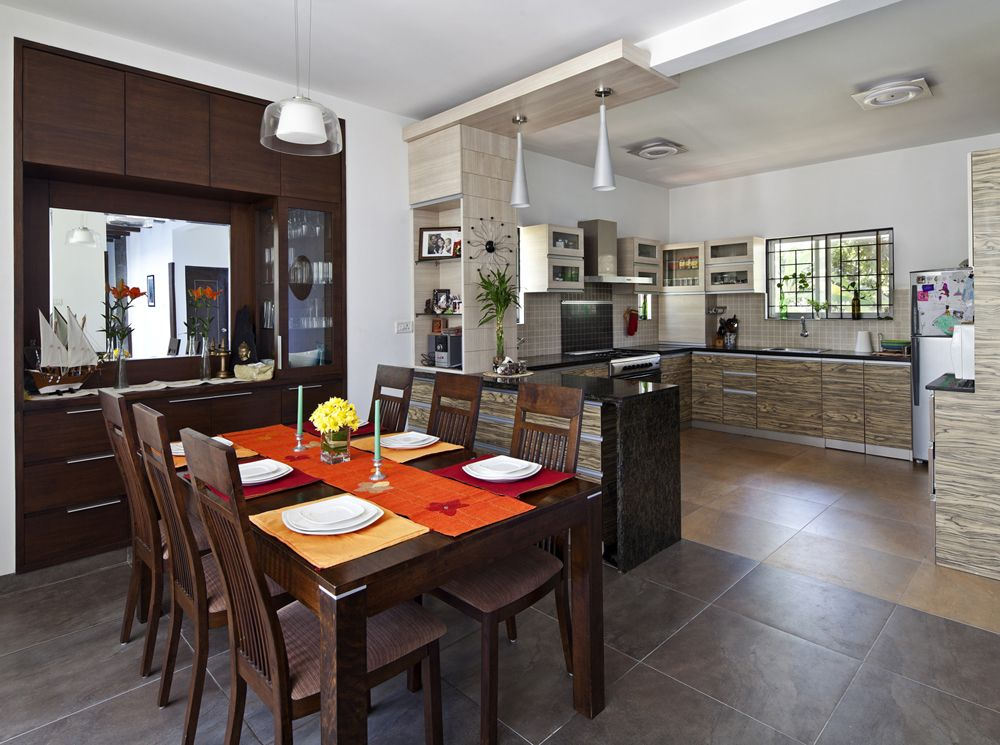 Dining area cum open kitchen with wooden furniture design by interior designer deep and hana Open dining room and kitchen designs