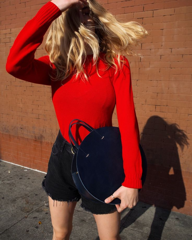 Loving this round tote bag and bold sweater combo