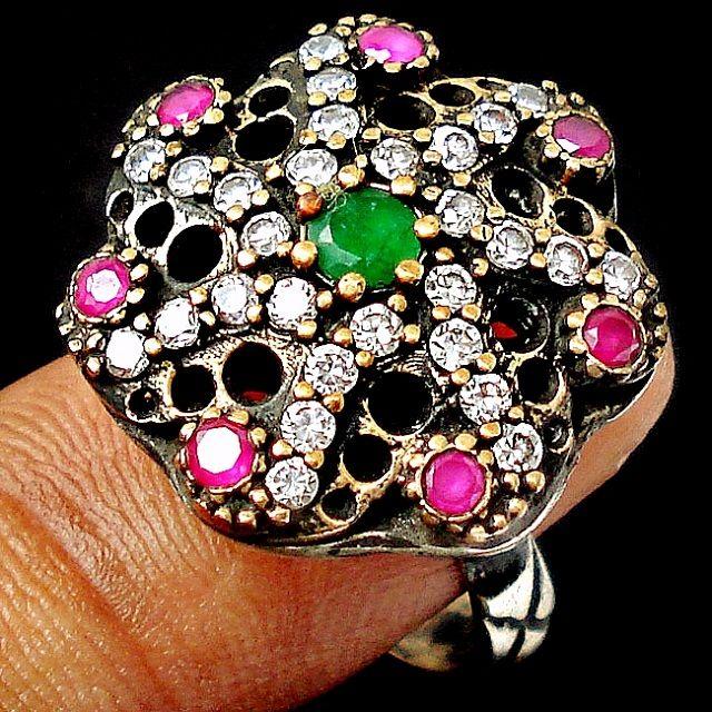 Anel de prata turco todo trabalhado, com aplicações de esmeralda, rubi e topázios.