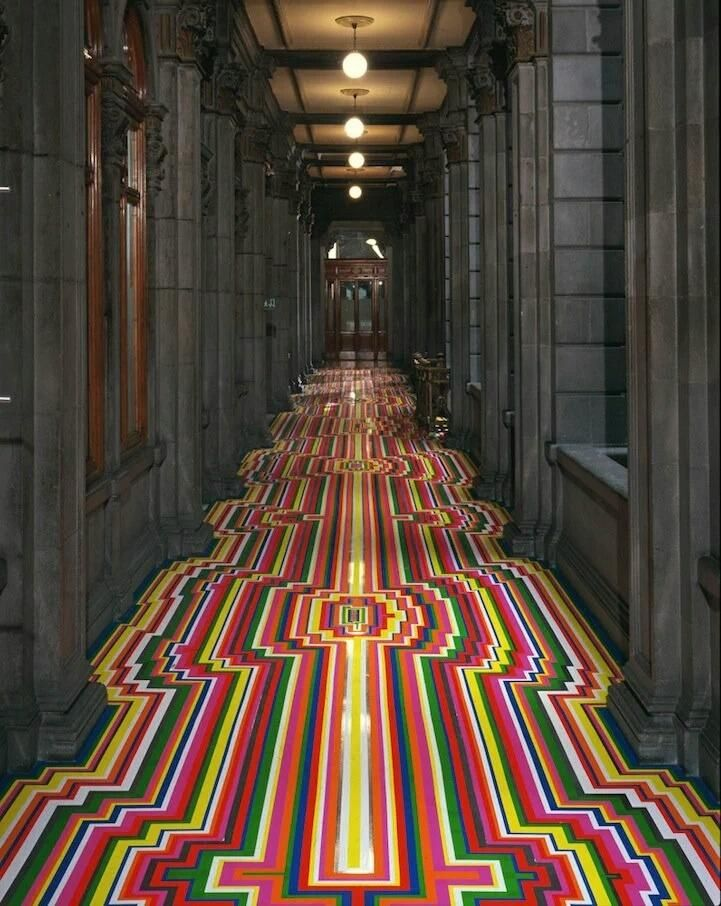 Colorful strips of geometric vinyl tape transform room design by Glasgow-based artist Jim Lambie.