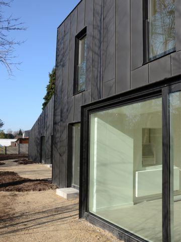 Une façade agrémentée de nombreuses ouvertures maison noire en belgique