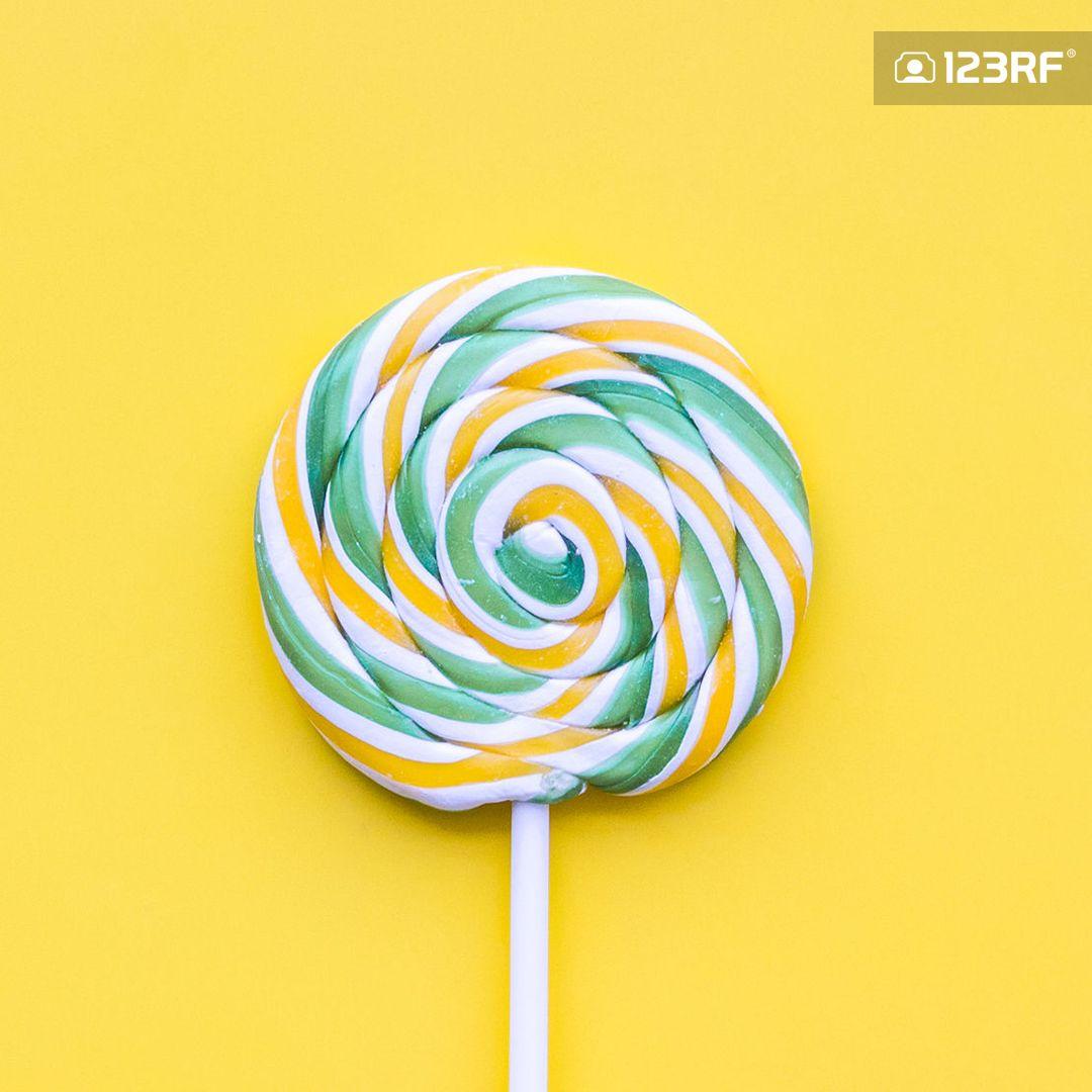 Colorful Lollipop Swirl On Yellow Pastel Background Top View Pastel Background Lollipop Swirl Lollipops