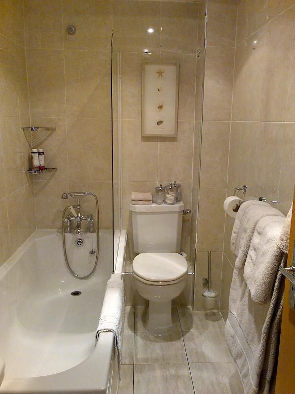 Fully tiled bathroom has over bath shower with excellent water