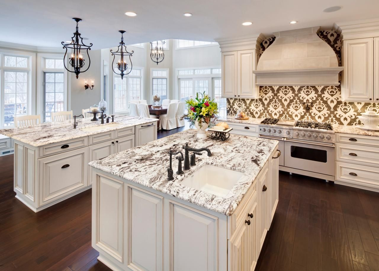 A Graphic Gold And White Backsplash Pops In This Elegant Sparkling Kitchen Two Islands With Marble Countertops Offer Plenty Of Counter E While