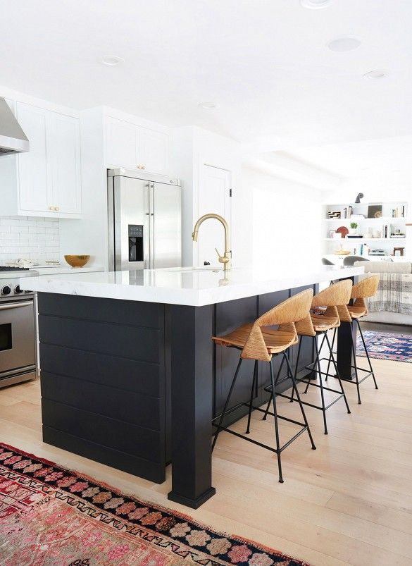 Black painted kitchen island with rattan counter stools