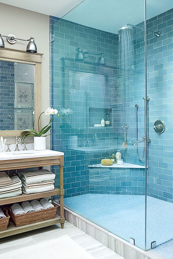 a bold blue tile shower space paired with a grey marbled