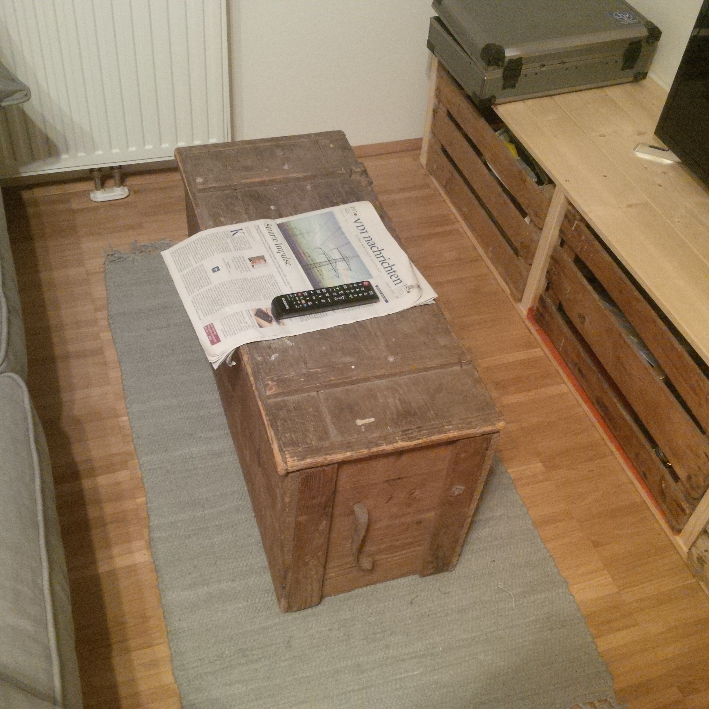 Old wooden box used as storage for blankets and pillows