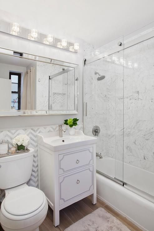 Chic Bathroom Features Upper Walls Painted Light Gray And Lower Walls Clad  In White And Gray