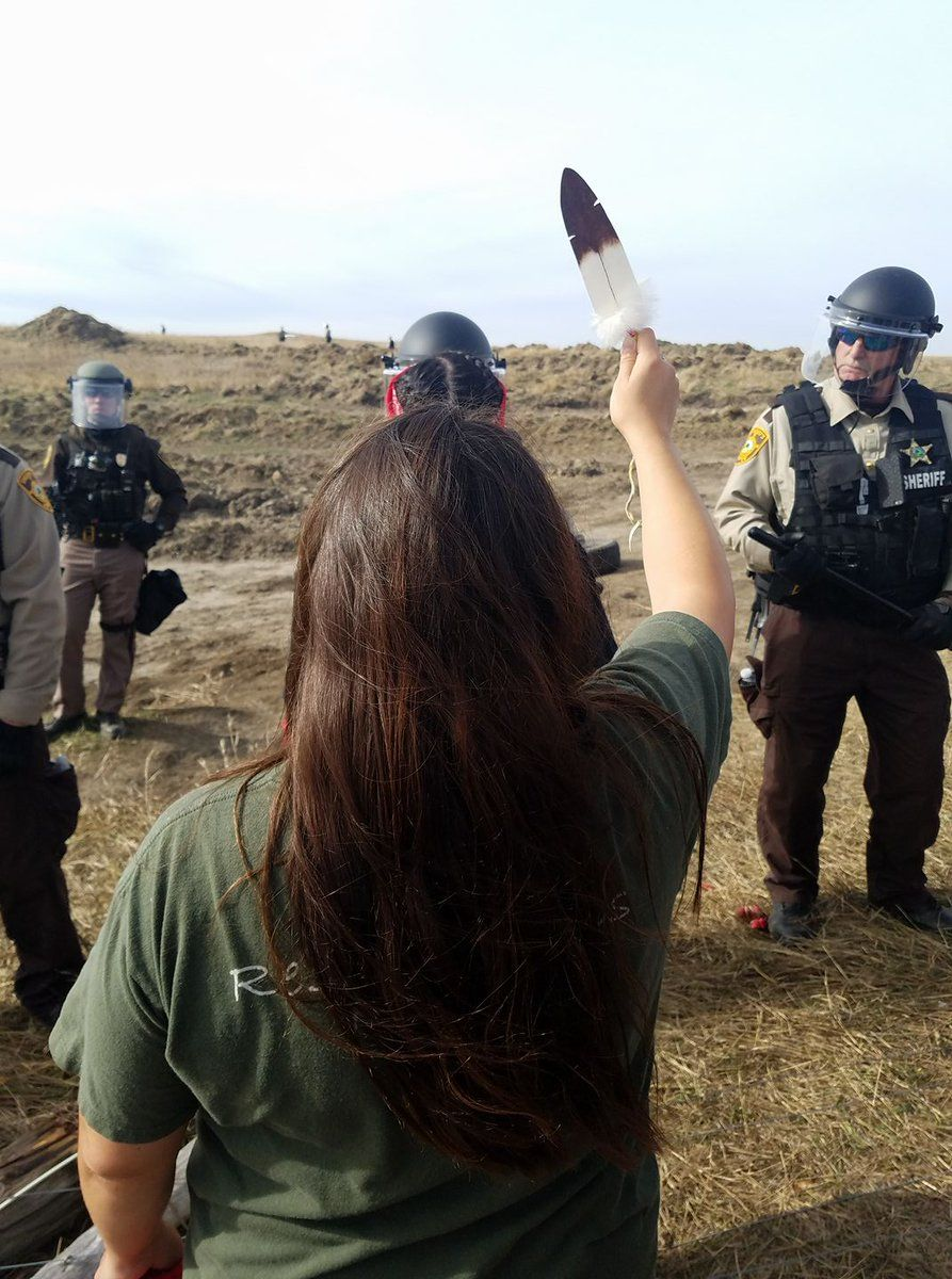 A Native American Water Protector Stands W Only An Eagle Feather In Hand Against Armed Police Pic Native American News Native People Native American History