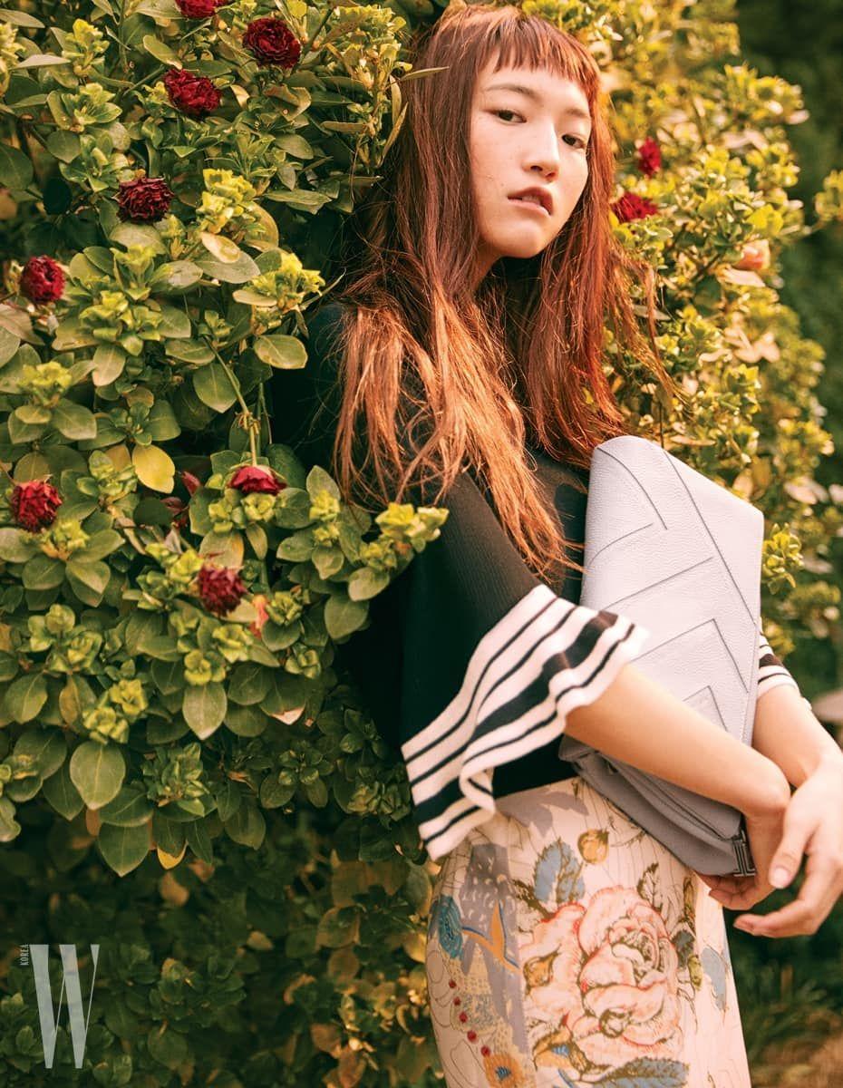 줄무늬가 들어간 검은색 벨 슬리브 니트. 꽃무늬 펜슬 스커트는 Lanvin Collection, 랑방컬렉션의 로고를 새긴 미에뜨 클러치는 Lanvin Collection Accessory 제품.