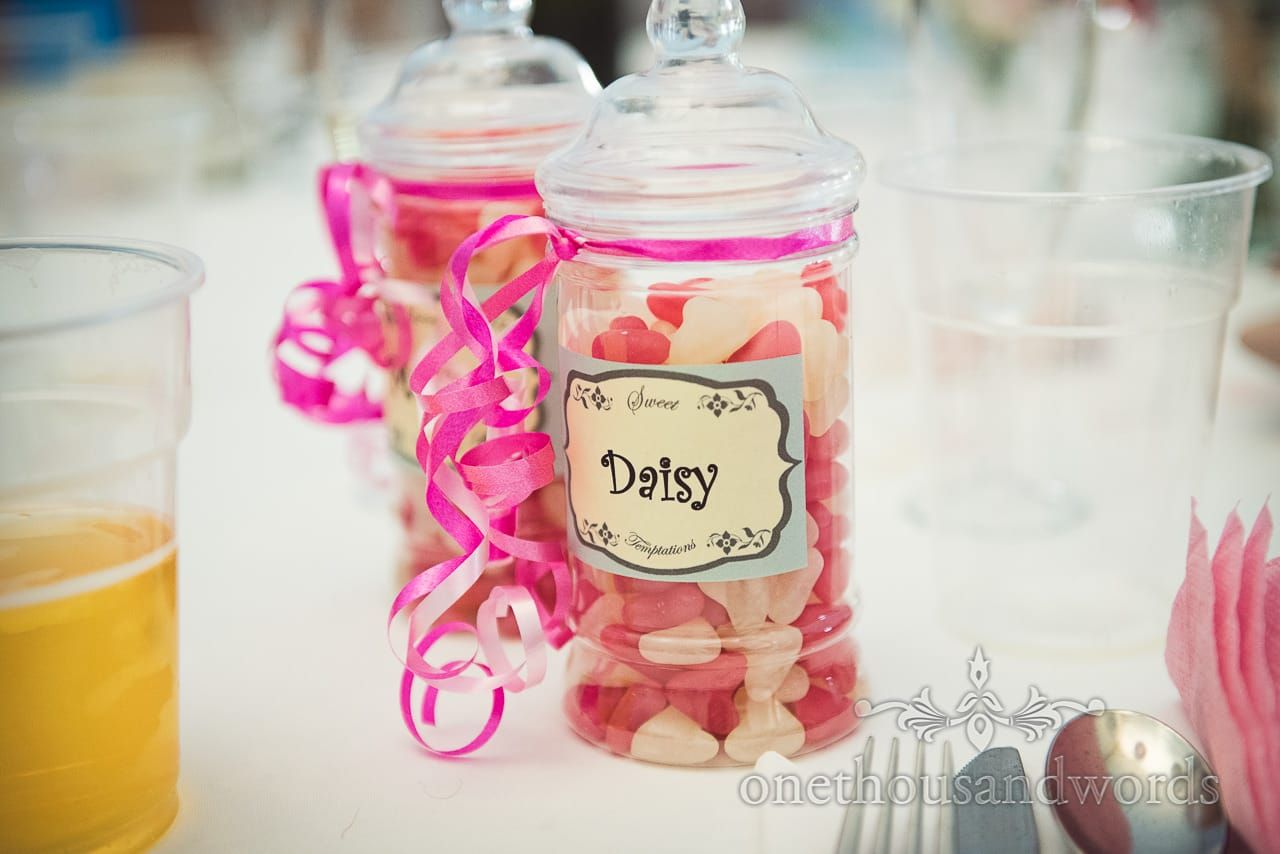 Wedding sweets in jar with pink ribbon as wedding favors with label ...