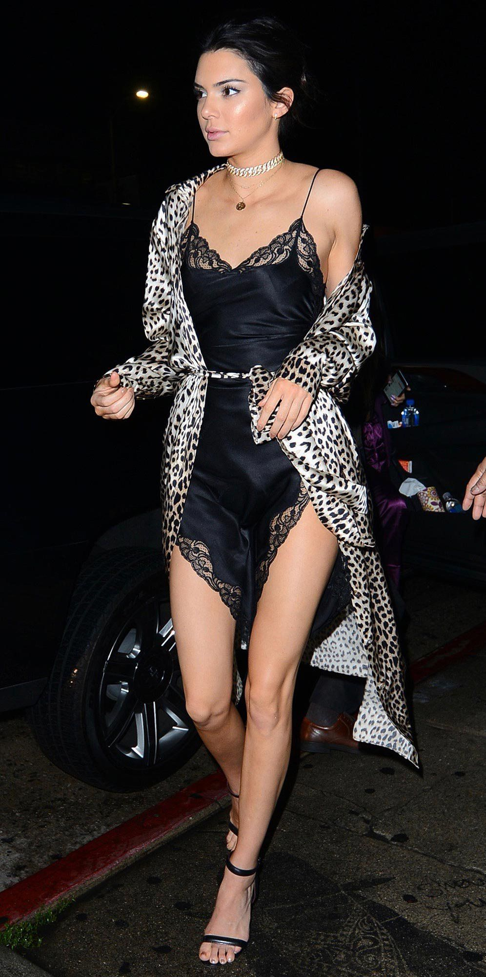 95753c8d61ae1 Kendall Jenner in a black lingerie-inspired dress and leopard duster coat  for New Year s Eve 2016 - click ahead to see Bella Hadid s sexy sheer  outfit!