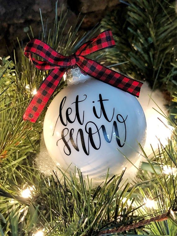 (1) white glass bulb ornament.Letit snow is applied using black vinyl.Adorned with a red and black buffalo check ribbon.