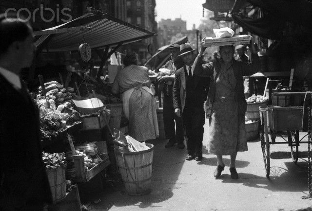 Woman Carrying Package On Her Head - 1935 New York: In Little Italy on the East Side. Old world customs and traditions are still faithfully observed here. This a corner of a pushcart mart on Mulberry Street. On her head, the woman carries sections of a packing box for fuel, and a loaf of bread.    #TuscanyAgriturismoGiratola