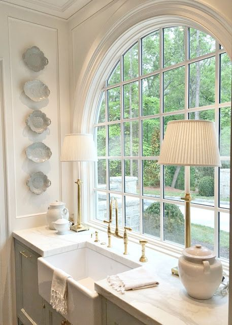 Stunning traditional style kitchen with light blue painted cabinets, hammered brass hardware arch window over farm sink, and waterfall marble island. Design Galleria Kitchen & Bath Studios. Lauren Deloach. Southeastern Designer Showhouse & Gardens.