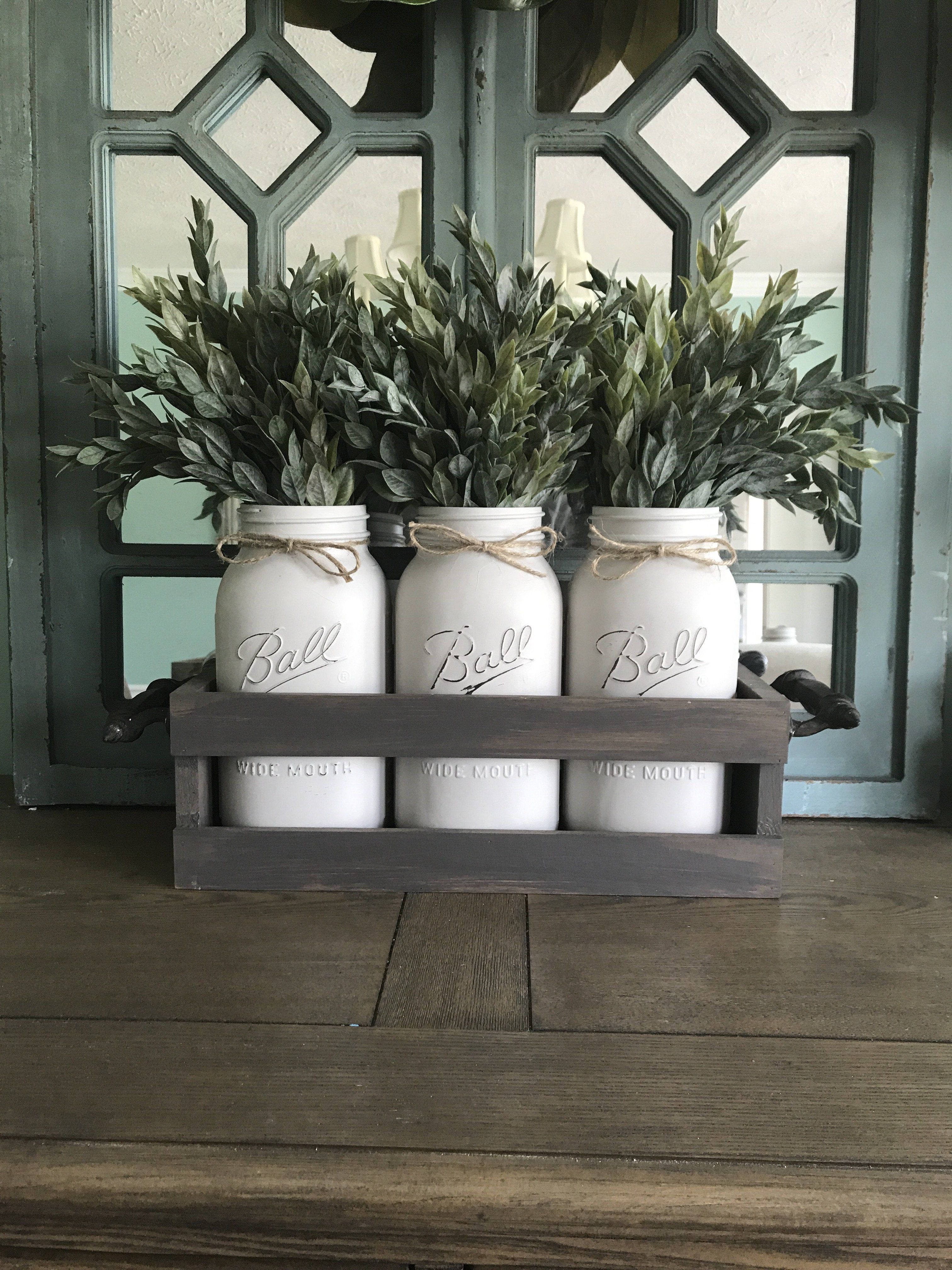 Farmhouse Mason Jar Centerpiece is part of Home Accessories Decor Mason Jars - Do you have a big farmhouse table that you're trying to find that perfect centerpiece for  This piece has three light gray half gallon Mason jars with a distressed barnwood style crate and black wrought iron handles  The beautiful ruscus greenery comes included as well!