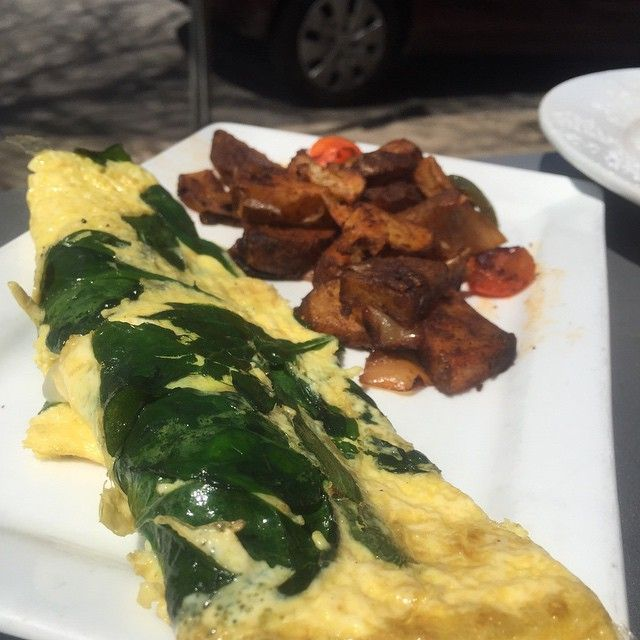 Spinach Omelet with Turkey Bacon and White Cheddar served with Seasoned Potatoes with Peppers and Onion